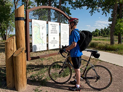 bicyclist looking at trail sign